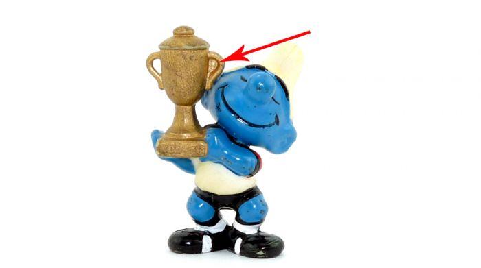 Spielführer Schlumpf, wo ein Henkel vom Pokal mit Farbe gefüllt ist